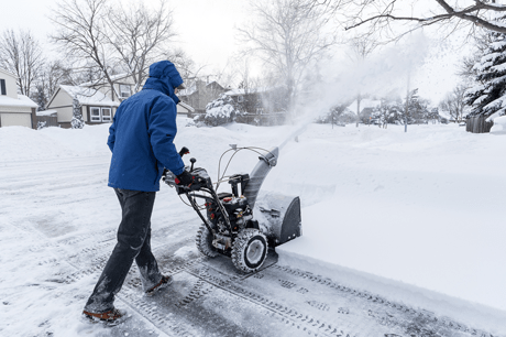 Man outside after snowfall with snowblower