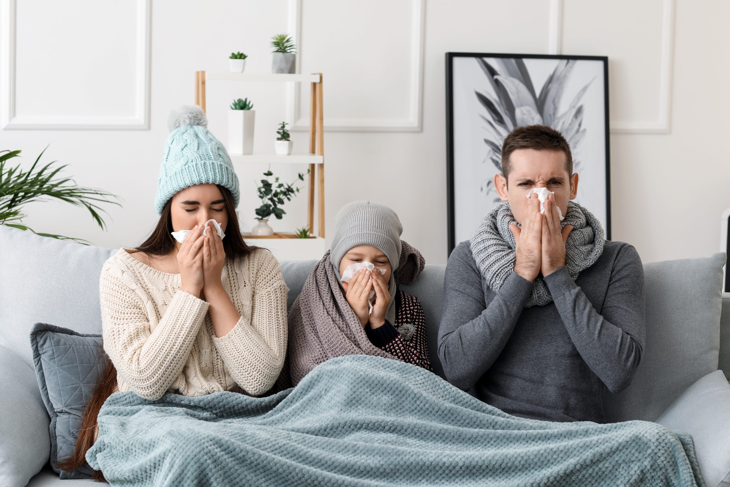 Family sitting on couch sneezing