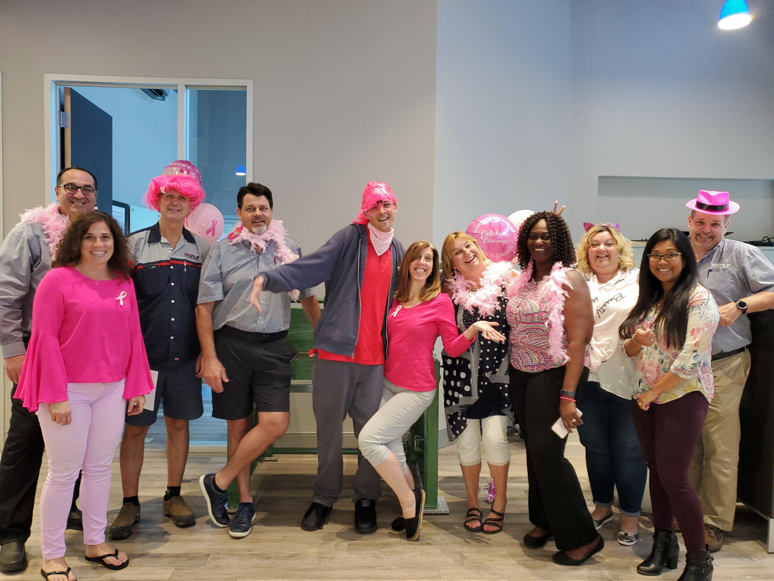 A1 in the community image of group of people wearing pink hats, boas etc.