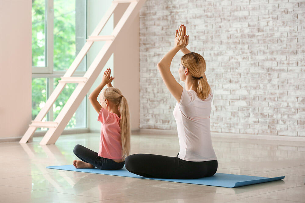 Mother and daughter doing yoga in an air purified home
