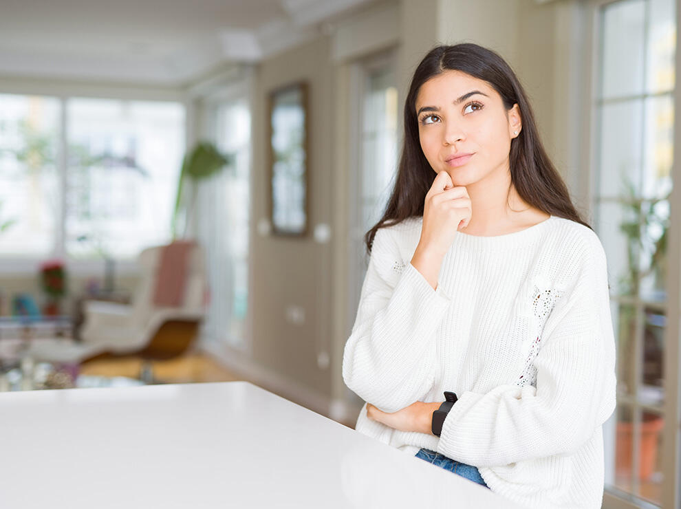 Woman sitting at counter thinking Indoor air quality