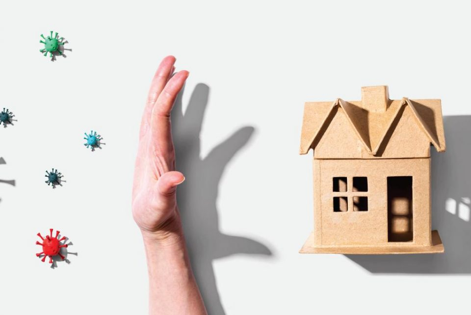 Image of cardboard home with hand protecting it from viruses entering. Indoor air quality