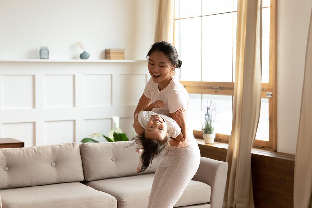 Woman holding and playing with child in living room cooling